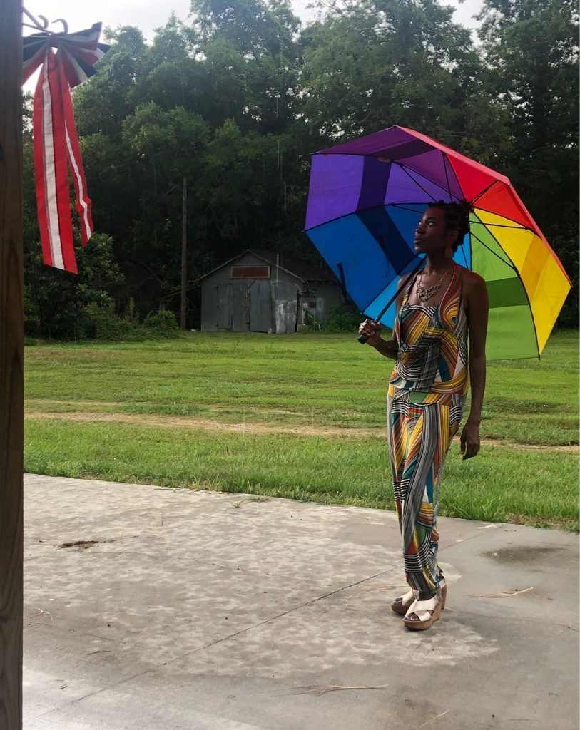 4th of July rural setting with a black woman with a rainbow looking at US flag decoration